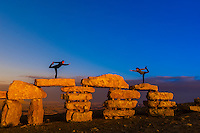 Women doing yoga poses atop rock sculptures at the sculpture park in Mitze Ramon, Negev Desert, Israel.