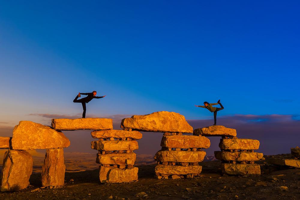 Women doing yoga poses atop rock sculptures at the sculpture park in Mitze Ramon, Negev Desert, Israel.