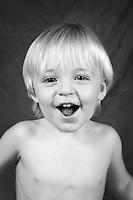 Toddler talking to camera in black and white studio, Caucasian blonde boy.