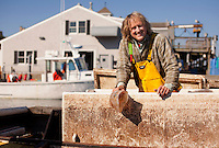 "Commercial handline fisherman, Ted Ligenza, cleans up his boat the ""Riena Marie"" as he talks to the reporter while tied up at the Chatham fish pier after a day of fishing in Chatham, Massachusetts on October 21, 2013."