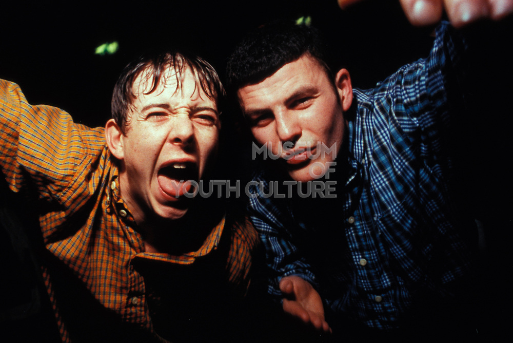 Two rowdy, northern lads wearing chequered shirts pose, Manchester, U.K, 1999.