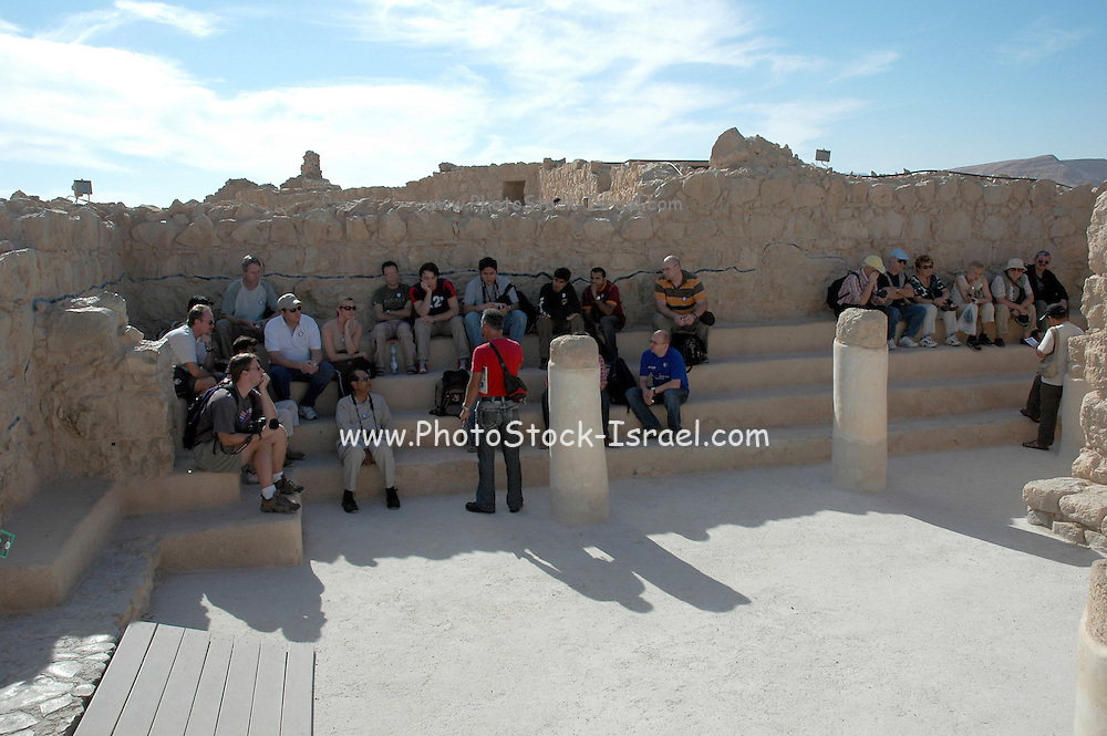Israel, Masada, A group of tourists listening to their guide at the Remains of the Metzada Synagogue Metzada is the site of ancient palaces and fortifications in Israel on top of an isolated rock cliff on the eastern edge of the Judean desert overlooking the Dead Sea. where Jewish zealot insurgents held out for three years against the Romans after the fall of Jerusalem in 70C.E. and then committed mass suicide to avoid capture. Metzada has remained a symbol of Jewish heroism.