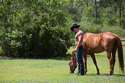 shirtless muscular cowboy with a horse on a ranch