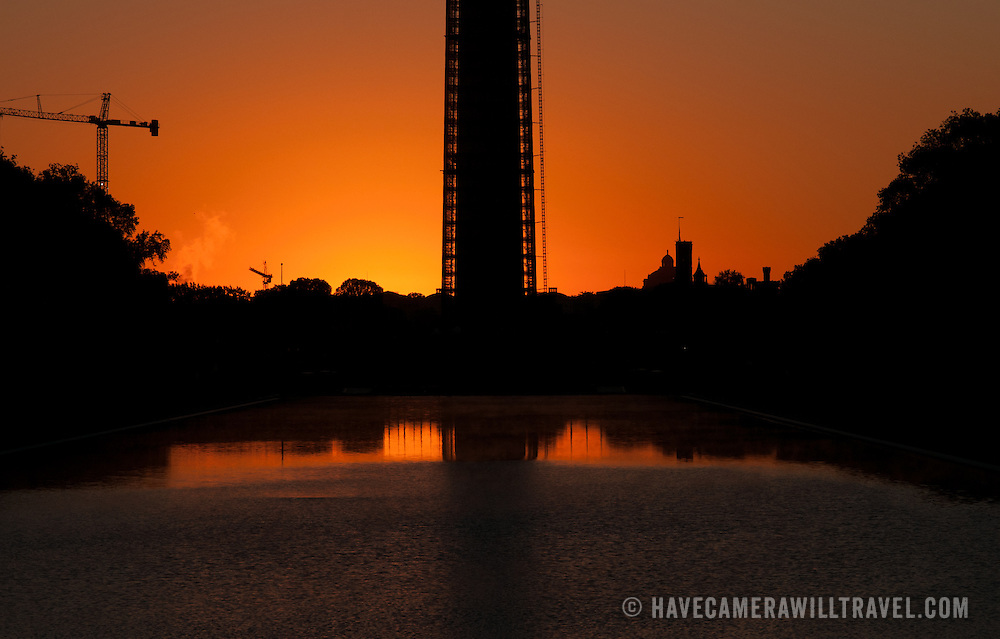 The orange glow before sunrise with a silhouette of the base of the Washington Monument and the Reflecting Pool in the foreground at bottom of frame.