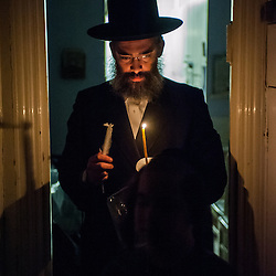 London, UK - 13 April 2014: a member of the Jewish Community of Stamford Hill searches for chametz (leavened bread products) in his house on the night before Passover.