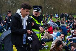 Hyde Park, London, April 19th 2015. Hundreds of cannabis users and their supporters gather at Speaker's Corner in Hyde Park for the annual London 420 pro-cannabis rally, under the watcful eye of Metropolitan Police officers, who kept a reasonably low profile, allowing the rally to continue without any serious incidents. PICTURED: A senior police officer detains a young man as the rally nears its end.