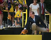 Tour de France director Christian Prudhomme picks up a fallen stuffed animal for the sun of Tour winner Carlos Sastre, during the finale prize ceremony of the 2008 Tour // Tourdirecteur Christian Prudhomme raapt het op de grond gevallen leeuwtje op voor het zoontje van Tourwinnaar Carlos Sastre.
