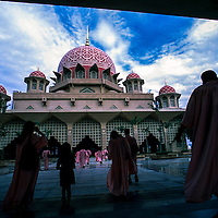 Tourists walks inside the compound of Putra Mosque in Putrajaya, Malaysia.<br /> Putra Mosque in Putrajaya reflects the evolution of mosque design in Malaysia, with its Islamic inspired architecture. Putrajaya is the Malaysia's administrative capital.