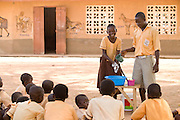 A boy and a girl in school uniforms demonstrate how to wash their hands with soap to classmates.