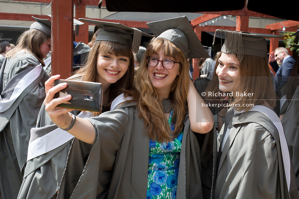 Young women graduands wearing rented gowns and mortarboards take a selfie with a smartphone at a private drinks party before their university graduation ceremony, on 13th July 2017, at the University of York, England.