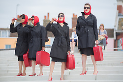 @Licensed to London News Pictures 25/07/2014. Margate, Kent. Clod Ensemble's Red Ladies undertaking missions in Margate as part of Turner Contemporary's Summer of Colour, culminating in performances at Margate's Theatre Royal this weekend (25/26 July) Photo credit: Manu Palomeque/LNP