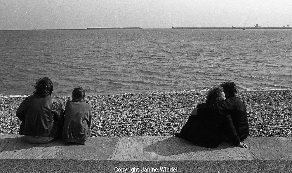 Two couples at the windy seaside sitting on the coastal wall