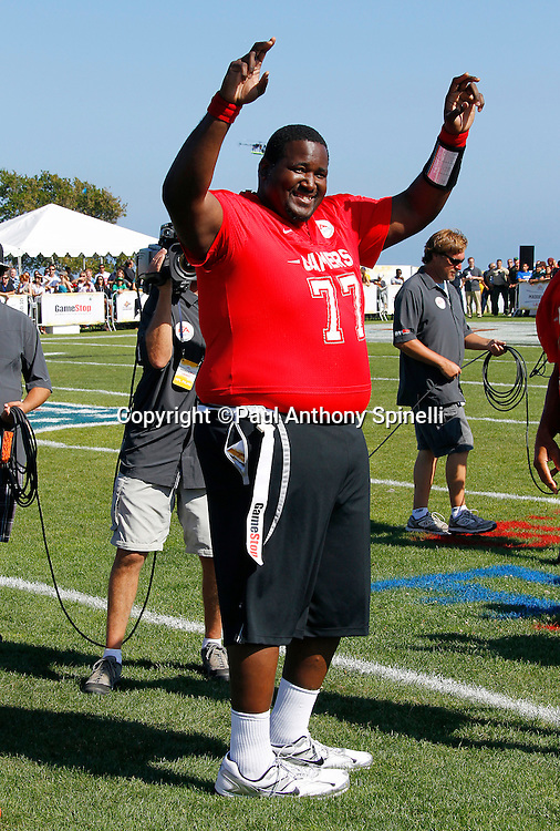 Actor Quinton Aaron (77) who played Baltimore Ravens offensive tackle Michael Oher in the 2009 movie The Blind Side waves to fans before playing flag football in the EA Sports Madden NFL 11 Launch celebrity and NFL player flag football game held at Malibu Bluffs State Park on July 22, 2010 in Malibu, California. (©Paul Anthony Spinelli)