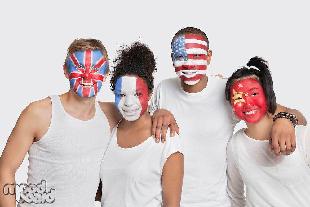 Portrait of happy Multi-ethnic group of friends with various national flags painted on their faces standing against white background