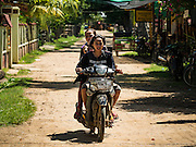 18 JUNE 2016 - DON KHONE, CHAMPASAK, LAOS: Lao women ride their motorscooter through Don Khone town on Don Khone. Don Khone Island, one of the larger islands in the 4,000 Islands chain on the Mekong River in southern Laos. The island has become a backpacker hot spot, there are lots of guest houses and small restaurants on the north end of the island.     PHOTO BY JACK KURTZ