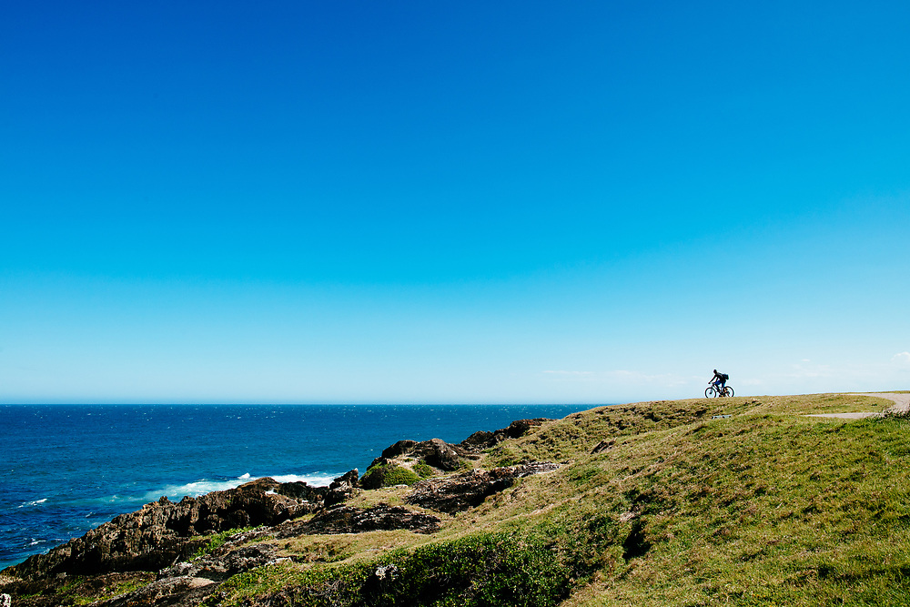 A cyclist looks out across the Pacific Ocean from Bonville Headland, Sawtell.