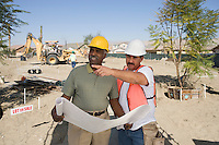 Surveyor and contraction worker at construction site