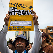 "KAWASAKI, JAPAN - JULY 16: Anti-racist man holds a banner during a counter-protest rally against ""hate speech"" rally in Nakahara, Kawasaki City, Kanagawa prefecture, Japan on July 16, 2017. (Photo by Richard Atrero de Guzman/NUR Photo)"