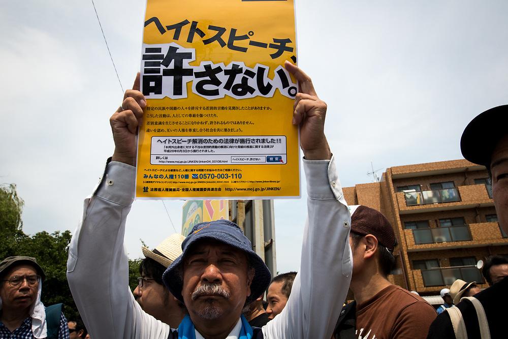 "KAWASAKI, JAPAN - JULY 16: Anti-racist man holds a banner during a counter-protest rally against ""hate speech"" rally in Nakahara, Kawasaki City, Kanagawa prefecture, Japan on July 16, 2017. (Photo by Richard Atrero de Guzman/NUR Photo)"