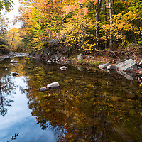 Colors of fall reflect in the tranquil stream at Scuptured Rocks, NH