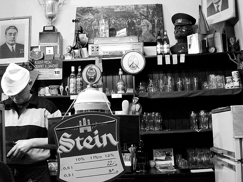 .The barman counts change on the last night of one of the last socialist style bars in Bratislava.  A bust of Lenin and framed photograph of Breznev can be seen behing him. from neighborhoods series