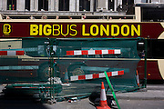 London city tour bus stopped at lights by construction work in central London.