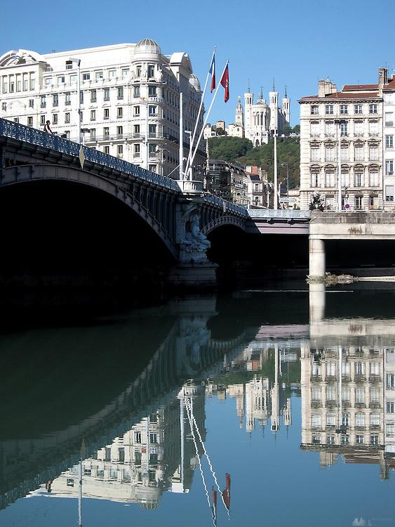 Imposing buildings reflected in a mirror-like Rhône river in Lyon, France