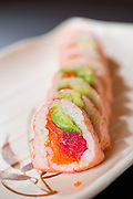A sushi roll with pink rice paper, tuna, salmon and avocado.