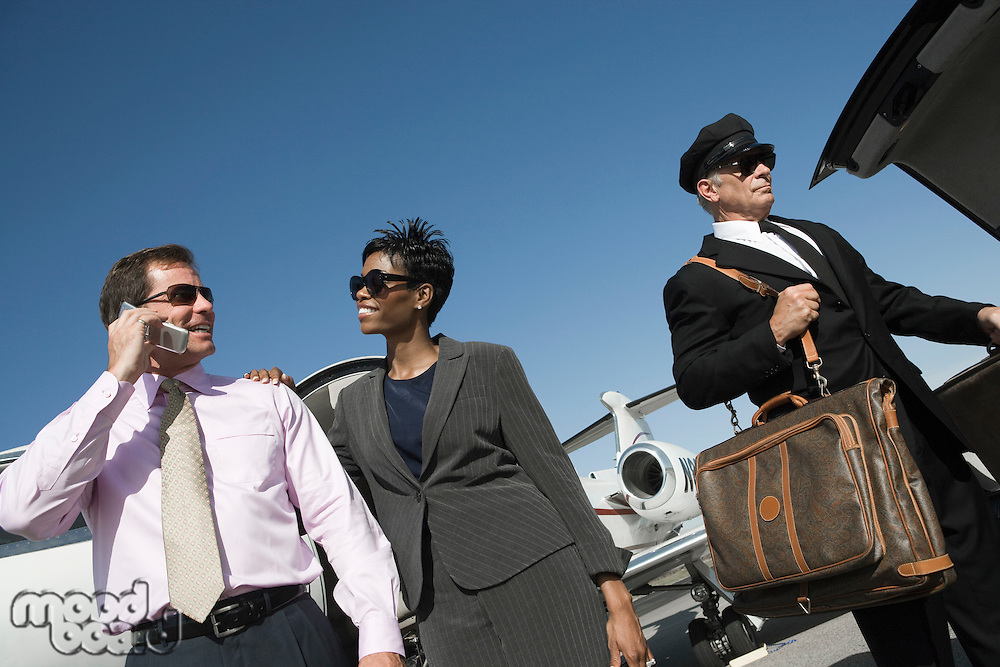 Mid-adult businesswoman, businessman and chauffeur in front of airplane on runway, low angle view.