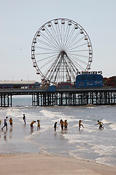 Beach scene with holidaymakers and Big Wheel at Blackpool pier.