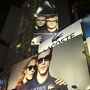 "The Lacoste billboards in Times Square, Manhattan, New York. Times Square is the major commercial intersection in Midtown Manhattan, New York City, at the junction of Broadway and Seventh Avenue and stretching from West 42nd to West 47th Streets. Times Square, iconified as ""The Crossroads of the World"" is the brightly illuminated hub of the Broadway theater district and one of the world's busiest pedestrian intersections. Time Square, New York, USA.  Photo Tim Clayton"
