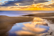 A tide pool at Kitty Hawk beach on the Outer Banks of NC reflecting a tranquil sunrise.