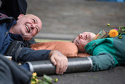 © Licensed to London News Pictures. 07/10/2019. London, UK. Two Extinction Rebellion protestor share a joke while glued to the ground near Parliament Square in Westminster. Activists will converge on Westminster blockading roads in the area for at least two weeks calling on government departments to 'Tell the Truth' about what they are doing to tackle the Emergency. Photo credit: Ben Cawthra/LNP