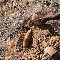 22/01/2013. Sévaré, Mali. Un témoin déblaye la terre où la jambe d'un corps apparait sous la terre dans un terrain vague du quartier Miliionkin de Sevare. Des exactions de l'armée malienne contre des suspectés d'être du camp opposé sont récemment sorties à la lumière. ©Sylvain Cherkaoui