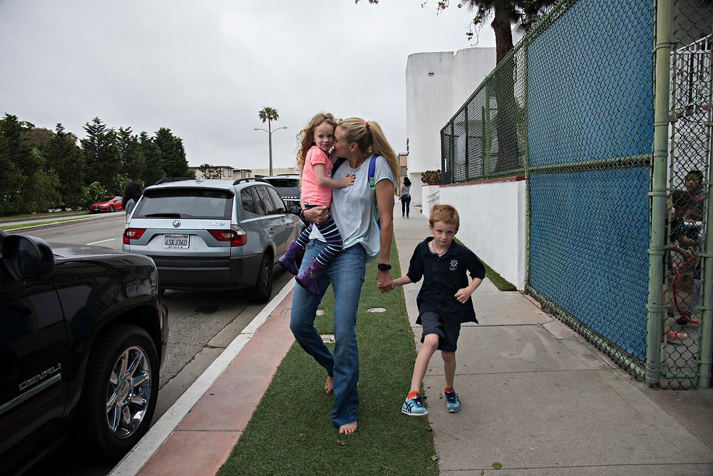 """I absolutely love being a mom, our kids bring out the best in me,"" said Kerri Walsh Jennings who strives for normalcy by picking up her youngest two from school. She heads to the car, barefoot, carrying daughter Scout, 4, out to the car, while son Sundance, 7, holds her hand."