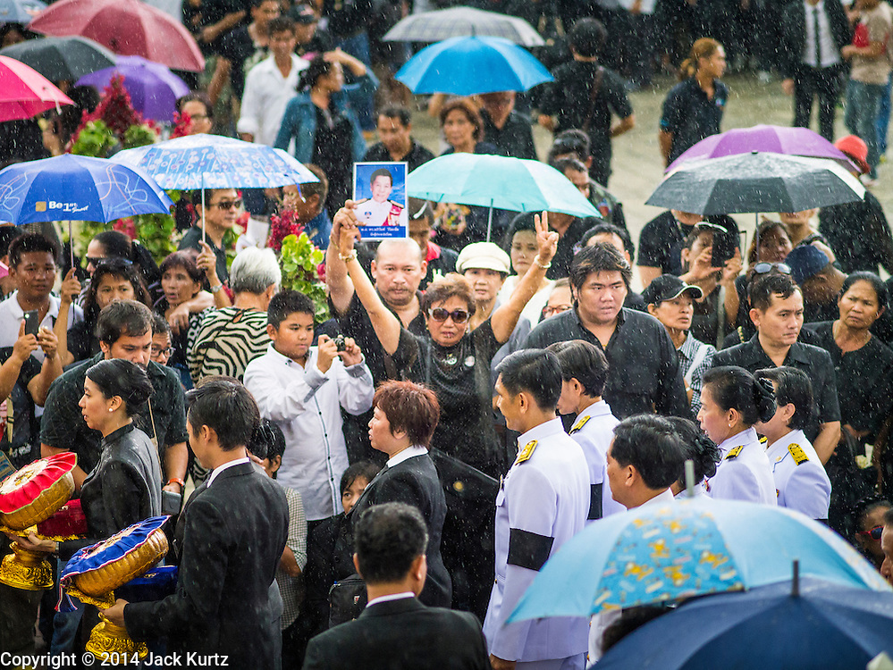 19 OCTOBER 2014 - BANG BUA THONG, NONTHABURI, THAILAND: A mourner standing in the rain holds up a photo of Apiwan Wiriyachai while the Wiriyachai family walks past during Apiwan's cremation at Wat Bang Phai in Bang Bua Thong, a Bangkok suburb, Sunday. Apiwan was a prominent Red Shirt leader. He was member of the Pheu Thai Party of former Prime Minister Yingluck Shinawatra, and a member of the Thai parliament and served as Yingluck's Deputy Prime Minister. The military government that deposed the elected government in May, 2014, charged Apiwan with Lese Majeste for allegedly insulting the Thai Monarchy. Rather than face the charges, Apiwan fled Thailand to the Philippines. He died of a lung infection in the Philippines on Oct. 6. The military government gave his family permission to bring him back to Thailand for the funeral. His cremation was the largest Red Shirt gathering since the coup.     PHOTO BY JACK KURTZ