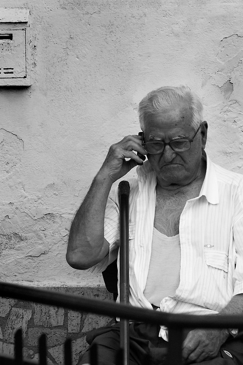 Man sitting and talking on the phone in Italy.