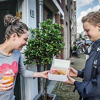 Nederland, Amsterdam, 3 juli 2016.<br /> De Croissant Boys, een familiebedrijf bestaande uit 3 broers die zondagochtend tussen 9-12 uur verse croissants met roomboter en/of jam en verse jus d'orange bij u thuis bezorgt.<br /> Op de foto: Willem Rosier levert croissants af bij een klant.<br /> <br /> The Croissant Boys, a family business consisting of three brothers who deliver fresh croissants with butter and / or jam and fresh orange juice to your home on sunday mornings between 9-12 am.  <br /> <br /> <br /> Foto: Jean-Pierre Jans