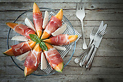 Overhead shot of plate with melon slices wrapped in prosciutto and mozzarella.