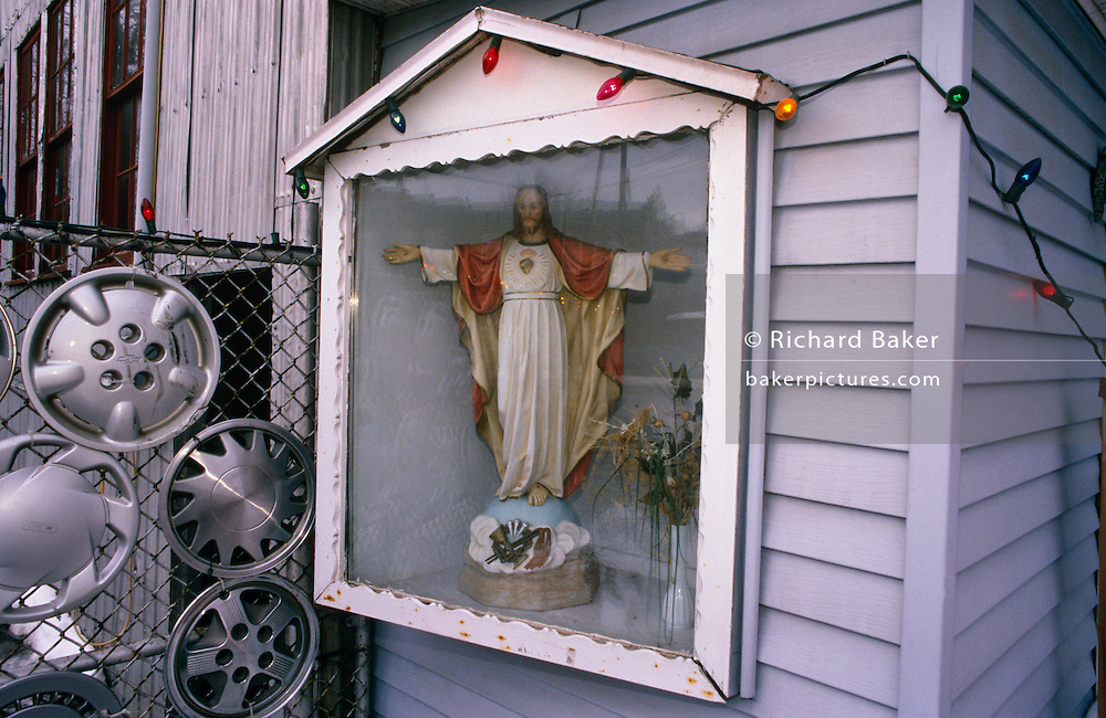 A Christian crucifix stands encased in a wooden box that has been attached to a panelled wall in Quebec, Canada. The image is white except for the Jesus icon itself and coloured lights which glow on this dark afternoon in the depths of Winter. The religious shrine consists of the human effigy standing a plinth next to faded dried flowers. On the left side are six wheel hubs also fixed to a wire fence that borders this person's property. Their decorative design suggests the Canadian owner likes driving sports or utility vehicles but who is also a worshipper of the Christian faith and believer in idols. Canada's 2001 Census showed, 72% of the Canadian population listed Roman Catholicism or Protestantism as their religion. The Roman Catholic Church in Canada is by far the country's largest single denomination.