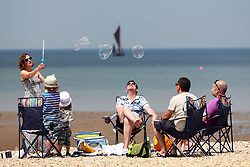 Image licensed to i-Images Picture Agency. 21/06/2014. Whitstable, United Kingdom. A group of friends enjoy the hot weather at Whitstable in Kent.  Picture by Stephen Lock / i-Images