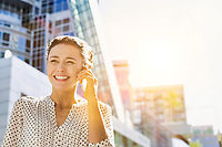Portrait of young attractive businesswoman smiling while talking on smartphone
