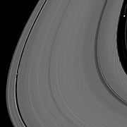 Saturn's moons Daphnis and Pan demonstrate their effects on the planet's rings in this view from the Cassini spacecraft.