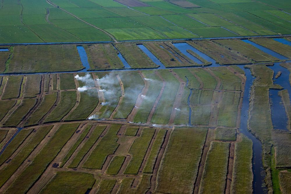 Nederland, Overijssel, Gemeente Steenwijkerland, 08-09-2009. Nationaal Park De Weerribben. Het landschap is het resultaat van het winnen van turf, na het steken van de turf (waardoor de 'trekgaten' ontstonden) werd dit te drogen gelegd op legakkers (de 'ribben'). Tegenwoordig vindt er rietteelt plaats (dekriet), de rook is het gevolg van het branden van rietvelden.Het gecontroleerd branden van rietvelden wordt toegepast om het riet wat door intensief maaien (door rietdekbedrijven) verruigd is en door ziekte is aangetast, weer nieuw leven in te blazen. .The National Park Weerribben. The landscape is the result of the extraction of peat, after digging the peat (creating  the 'pull holes'), it was to layed to dry on fields (the 'ribs'). Today production of reed takes place (thatching), the smoke was caused by burning cane fields.The controlled burning of the reed  fields  to renew the reed.toeslag); aerial photo (additional fee required); .foto Siebe Swart / photo Siebe Swart