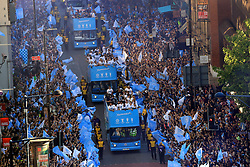 The players and staff on the buses pass the crowds of fans during the trophy parade in Manchester.