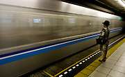 A train moves by at high speed while a middle aged woman waits on the platform on the Tozei line, Takebashi station, Tokyo.