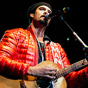Micahel Franti and Spearhead perform to a packed crowd in Teton Village, Wyoming. Portrait of Michael Franti performing with guitar.