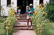 Carey Lung and daughter Hailey Lung near their sunflower patch at home, Tucson, Arizona..Subject photograph(s) are copyright Edward McCain. All rights are reserved except those specifically granted by Edward McCain in writing prior to publication...McCain Photography.211 S 4th Avenue.Tucson, AZ 85701-2103.(520) 623-1998.mobile: (520) 990-0999.fax: (520) 623-1190.http://www.mccainphoto.com.edward@mccainphoto.com