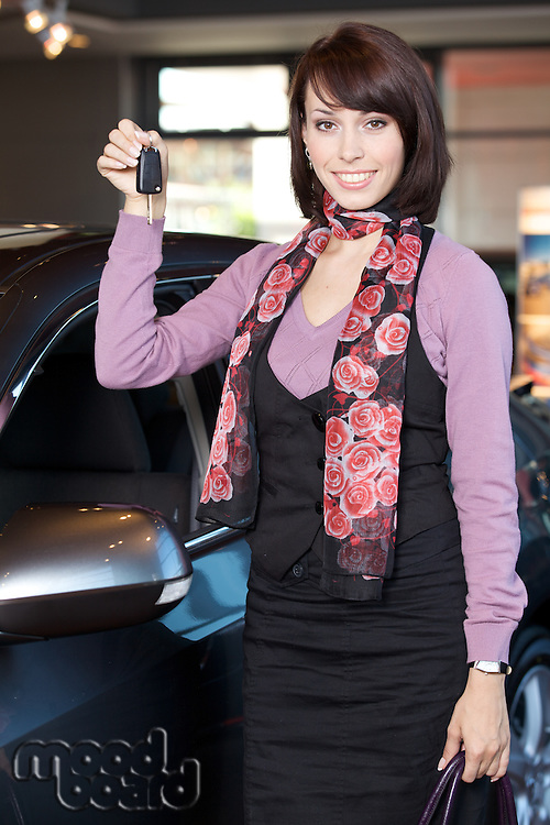 Portrait of smiling young woman holding car key