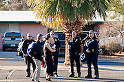 tucsonshooting - 09 JANUARY 2011 - TUCSON, AZ: A family talks to Tucson police officers in the parking lot at Congregation Chaverim in Tucson Sunday. Hundreds of people attended the healing service to pray for Congresswoman Gabrielle Giffords and other victims of the mass shooting that took place Saturday.     PHOTO BY JACK KURTZ